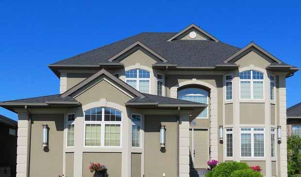 Une maison avec un toit graphite(gris)  et une façade beige