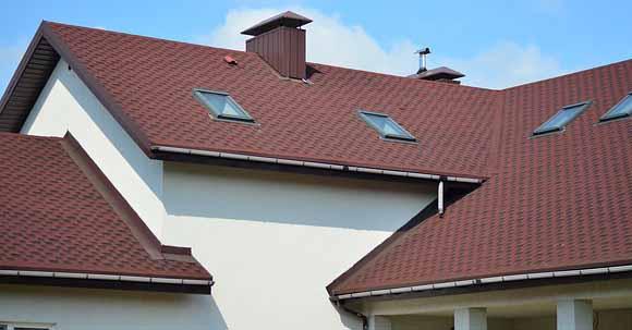 Une maison avec un toit marron et une façade clair