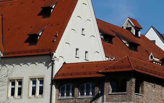 Une maison avec un toit rouge et une façade clair