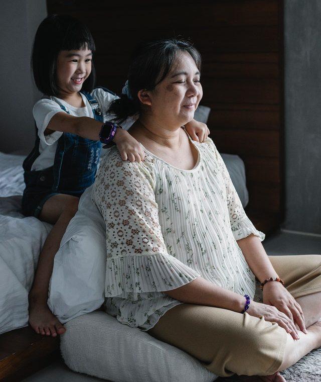 Une fille qui fait un massage à la maison à sa maman